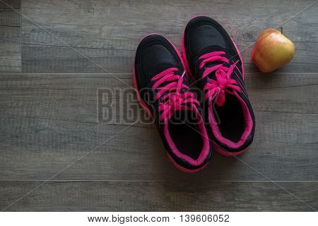 Pink sport shoes with apple on wooden background
