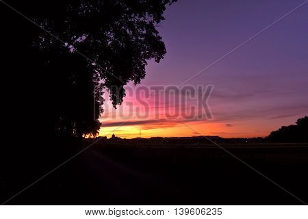 Evening scene with silhouettes of trees houses church pylon and Ceske Stredohori mountains in village Brozany nad Ohri in bohemian landscape