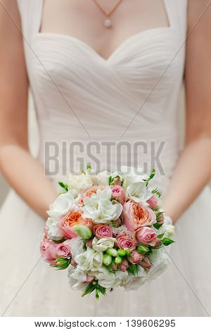 Hands of a bride holding a bouquet on the wedding day