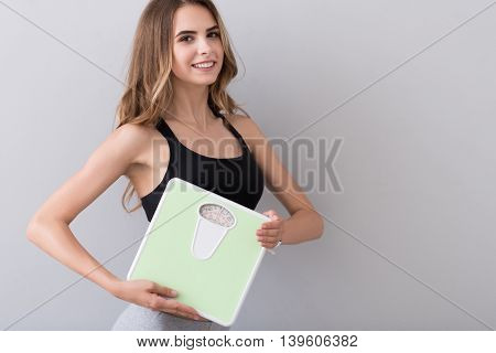 Train down. Positive beautiful slim woman smiling and holding scales while standing isolated on grey background