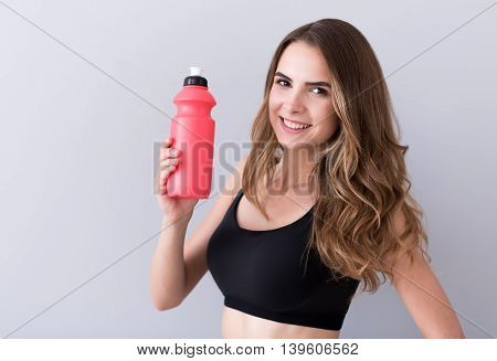 My portion of energy. Pleasant delighted smiling woman holding bottle with water and expressing positivity while standing isolated on grey background