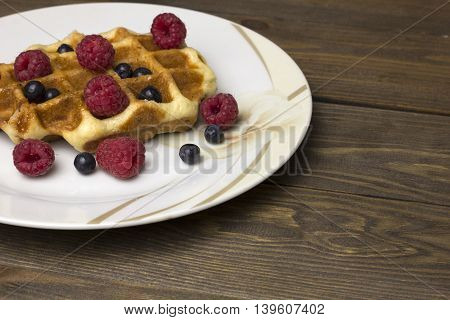 waffles in a white plate with berries on the table , delicious breakfast