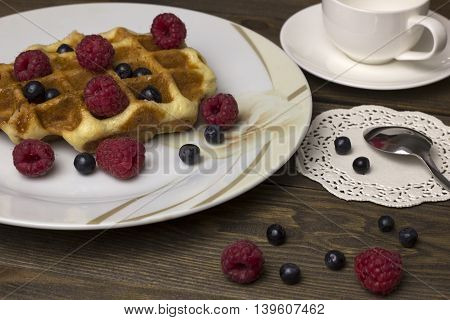 waffles in a white plate with berries on the table , blueberries, raspberries and a cup of tea delicious breakfast
