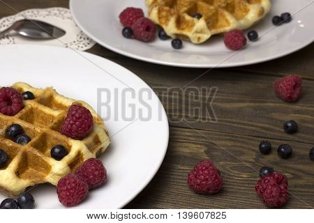 Two plates of waffles and berries raspberries and blueberries on a wooden table