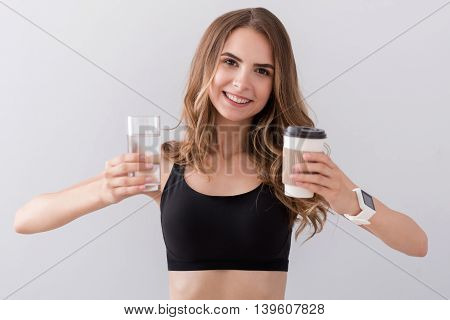 What to choose. Cheerful beautiful woman smiling and holding water and coffee while standing isolated on grey background