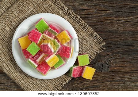 Candied fruit jelly in plate on old wooden background top view