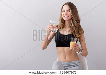Health makes happiness. Pleasant joyful beautiful woman sitting in the chair and holding glass of water and juice while smiling