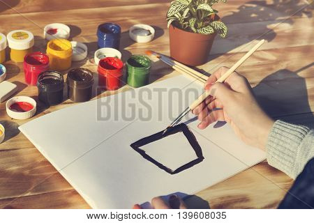 The artist paints with a brush. Empty album paints pencils and flowers on wooden background.