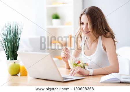 In touch with the world. Delighted beautiful woman eating vegetable salad and using laptop while sitting at the table