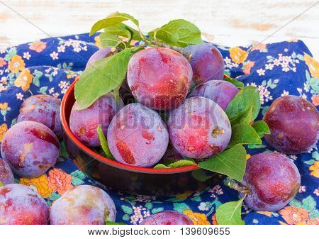 fresh ripe plums in a black plate on colored fabric closeup. selective focus