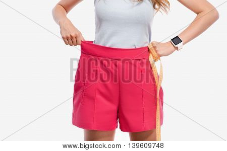 Good result. Pleasant slim woman holding measure tape and wearing her shorts while standing isolated on white background