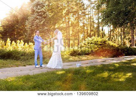 Happy bride and groom walking in a summer park