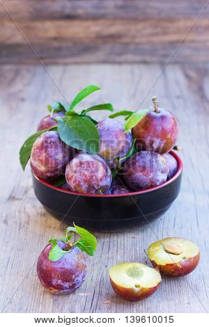 fresh ripe plums on old wooden boards close up. selective focus