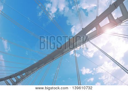 Steel structure. Hanging bridge against a cloudy sky. Empty copy space for editor's text.