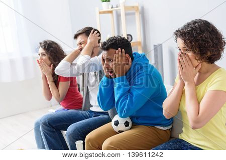 It can not be true. Four sad football fans cheering football match at home, holding hands on heads