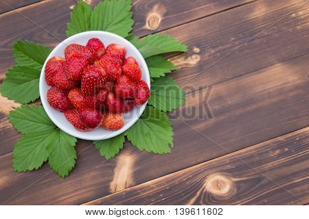 Fresh juicy strawberries in plate on wooden table top view
