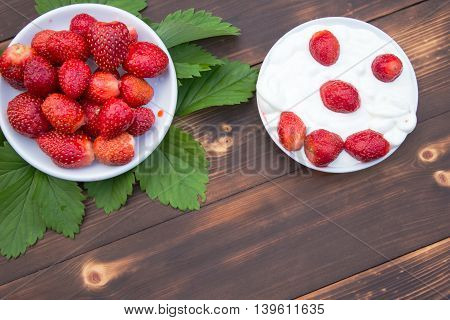 Strawberries and yogurt in a bowl on wooden table top view