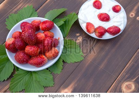 Fresh juicy strawberry with yogurt in the plate isolated on a wooden table