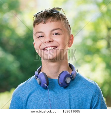 Beautiful smiling teen boy with headphones and sunglasses