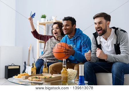 Basketball fans at home. Cheerful young friends watching TV and holding basketball ball while gesturing on couch at home