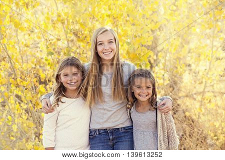 Beautiful Portrait of smiling happy kids outdoors. Three sisters standing together for a cute picture on a warm fall day