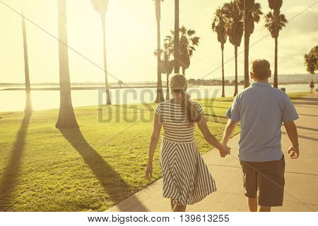 Middle aged couple walking together holding hands along the beach boardwalk. Abstract image of Building relationships and marital bonds. Early evening sunset and warm summer tone