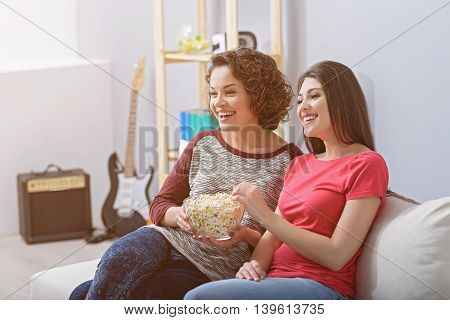 Injoying movie. Two beautiful girlfriends sitting on couch at home with popcorn and watching TV, smiling