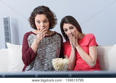 Absolutely shocked. Shot of two young girls sitting on their living room sofa and watching movie, eating popcorn