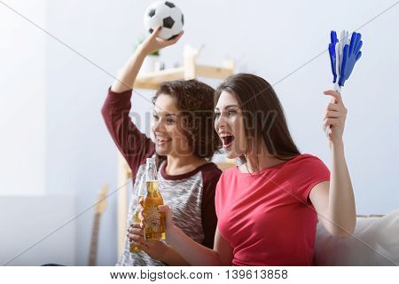 Cannot control their emotion. Cropped photo of young smiling girl watching football match at home and celebrating goal together