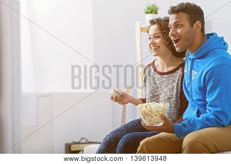Enjoying watching match together. Smiling couple sitting on couch near window and watching match during eating popcorn