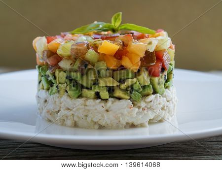 Homemade Crab Meat Salad with Heirloom Tomato Salsa and Sesame Seed Chopped Avocado on Wood Background/ Selective Focus/ Close-up