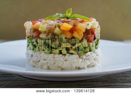Homemade Crab Meat Salad with Heirloom Tomato Salsa and Sesame Seed Chopped Avocado on Wood Background/ Selective Focus
