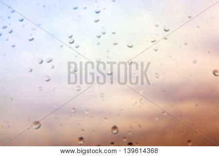 photographed close-up drops of rain left on the glass, raindrops on the window, the autumn and multicolored background, out of focus, defocus