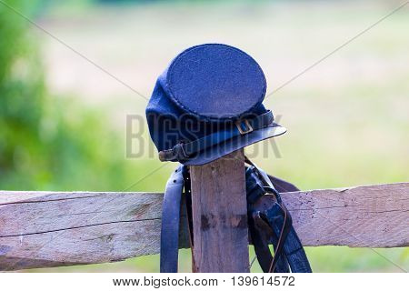 US Civil War Federal Army's Soldiers Cap is balanced on a fence post.