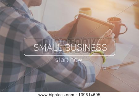 Screen. Inspirational typographic quote of small business with cropped image of man using digital tablet in a background