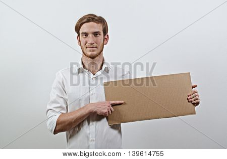 Young Adult Man in White Shirt Holding a Cardboard Inscription
