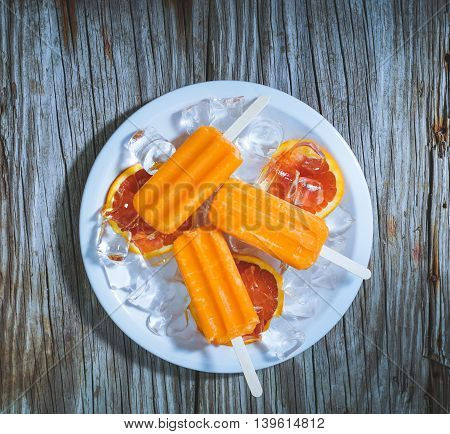 Homemade frozen bloody orange carrot popsicles on wood background.