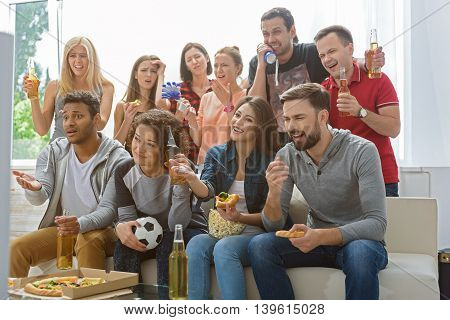 Why is it so unfair. Group of friends yelling at referee while they watching soccer game on TV at home