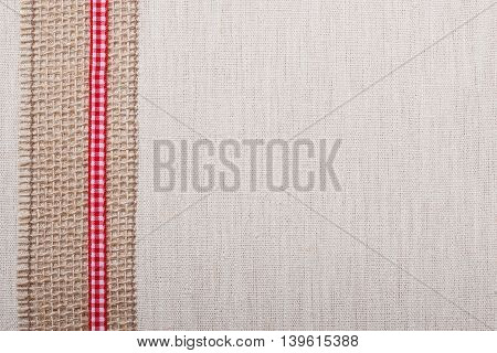 Jute mesh and red ribbon on bright fabric textile material natural linen background
