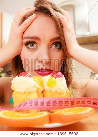 Undecided woman looking at delicious cake with sweet cream and fruits on top. Girl with tape measure trying to resist temptation. Slimming diet dilemma.