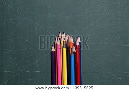 Colorful Pencils On Green Blackboard Or Desk