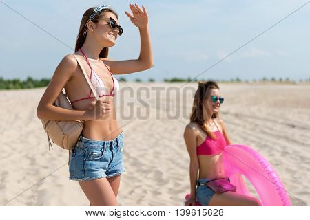 Open for fun. Cheerful delighted woman holding her bag on the shoulder and looking aside while resting on the beach with her friend