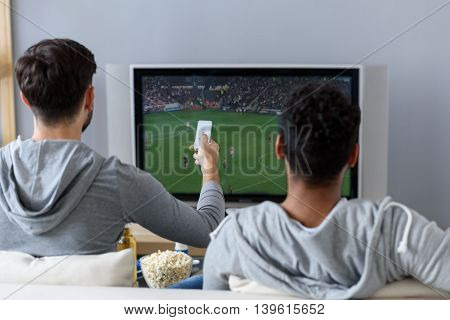 Fans of same game. Rear view of guy sitting on couch and watching football with his friend, holding remote in hand