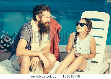 young handsome bearded man with long beard on beach chair and small happy girl in sun glasses on face with pen and notebook at swimming pool with blue water sunny summer vacation
