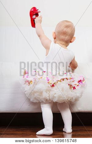 Lesson of walking. Sweet adorable baby girl thinking about make step. Little child toddler wearing princess dress with red small shoes.