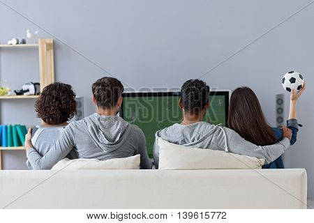 Giving total support. Rear view of two couples watching favorite game and sitting on white couch at home in front of plasma