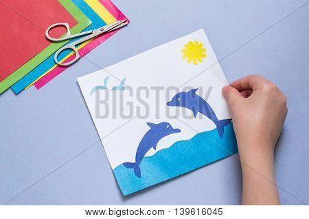 Paper applique is made by the child on a sea theme. The idea for children's creativity an art project made of paper. Sheets of colored paper glue scissors. Children's hand holding a picture