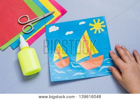 Paper applique is made by the child on a sea theme with sailboats. The idea for children's creativity an art project made of paper. Sheets of colored paper glue scissors. Children's hands holding a picture