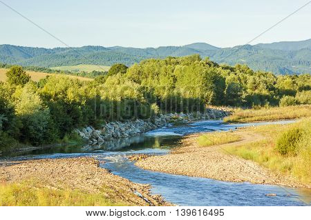 Clear blue river in mountains on summer day