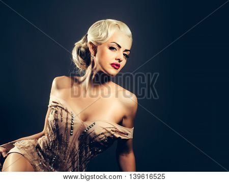Young woman blonde with vogue makeup in splendid beige dress with bare shoulders and sexi cleavage posing on dark background studio